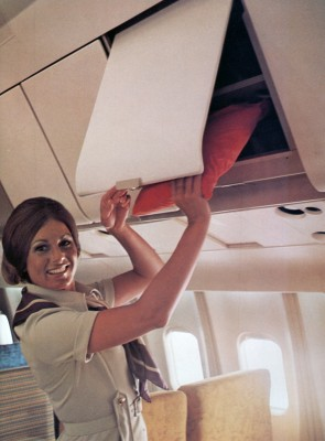 The overhead bins featured a fold-back shelf for larger items but still had limited space. (TWA)